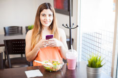 Gorgeous girl using a smartphone while having lunch Royalty Free Stock Photos