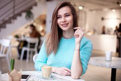 Gorgeous girl waiting friend in restaurant with cozy interior and drink cofe. Gorgeous girl with curly hairstyle waiting friend in restaurant with cozy interior Stock Photography