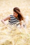 Gorgeous girl walking in the field of long grass and dragging he Royalty Free Stock Images