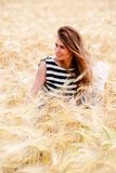 Gorgeous girl walking in the field of long grass and dragging he Stock Photography