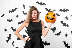 Gorgeous girl wearing black dress holds horror halloween pumpkins on the background of the wall with bats royalty free stock image