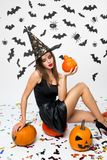 Gorgeous girl wearing black dress, witch hat and high heels sits on the pumpkin and holds Halloween pumpkin in her hand royalty free stock photo
