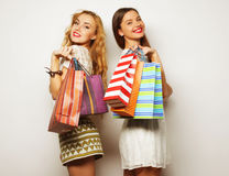 Gorgeous girlfriends with paperbags looking at camera Royalty Free Stock Photo