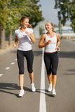 Gorgeous girls running on the blurred background. Sporty youth. Morning jogging concept. Stock Photo