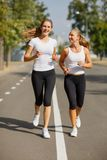 Gorgeous girls running on the blurred background. Sporty youth. Morning jogging concept. Royalty Free Stock Photos