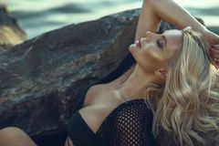 Gorgeous Glam Tanned Blond Woman With Closed Eyes Wearing Black Swimsuit And Summer Tunic Relaxing And Bathing In The Sun Royalty Free Stock Photos