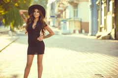 Gorgeous glam tattooed lady with long wavy hair in a little black dress and trendy fedora hat standing on the street and smiling. Portrait of a gorgeous glam Stock Photography
