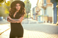 Gorgeous glam tattooed lady wearing a little black dress and trendy fedora hat standing on the street and smiling on a sunny day royalty free stock image