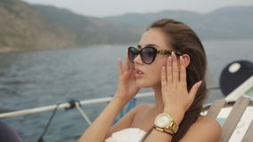Gorgeous green-eyed brunette in sunglasses has a rest on a yacht at sea. Gorgeous green-eyed brunette in sunglasses has a rest while lying on a yacht at sea stock video