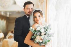 Gorgeous groom gently hugging stylish bride. Sensual moment of luxury wedding couple Stock Image