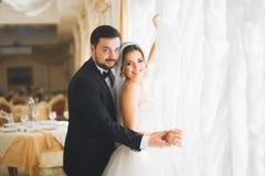Gorgeous groom gently hugging stylish bride. Sensual moment of luxury wedding couple.  stock photos