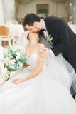 Gorgeous groom gently hugging stylish bride. Sensual moment of luxury wedding couple Royalty Free Stock Photos