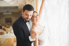 Gorgeous groom gently hugging stylish bride. Sensual moment of luxury wedding couple Royalty Free Stock Photo
