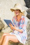 Gorgeous happy blonde using tablet pc at the beach Stock Photos