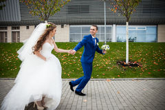 Gorgeous happy brunette bride and elegant groom in blue suit run. Ning on the background of modern building and autumn trees Royalty Free Stock Photography