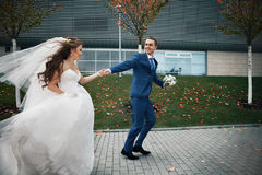 Gorgeous happy brunette bride and elegant groom in blue suit run. Ning on the background of modern building and autumn trees Royalty Free Stock Photo