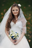 gorgeous happy brunette bride holding amazing bouquet on the background of nature royalty free stock photo