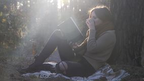 Gorgeous happy brunette female model in cozy sweater and jeans reading book and drinking hot tea or coffee in fall autumn at sunse. T stock video footage