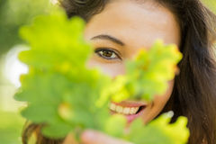 Gorgeous happy brunette holding a leaf Royalty Free Stock Images