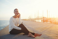 gorgeous happy female speaking on cell telephone with her friend while sitting on a pier near sea port Royalty Free Stock Photos
