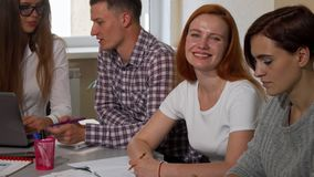 Gorgeous happy female student smiling to the camera, while studying with friends stock photography