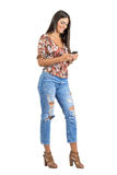Gorgeous happy Hispanic beauty typing message on her mobile phone. Full body length portrait isolated over white studio background royalty free stock photo