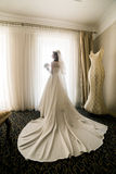 Gorgeous happy luxury stylish bride in white dress and veil near  window on the background of vintage room Stock Photo