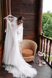 Gorgeous, happy smile bride trying wedding dress before wearing. Morning preparations. Woman putting on dress on wooden stock photo