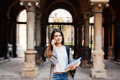 Gorgeous happy student holding notebooks speak phone on campus at college. Gorgeous happy student holding notebooks speak on phone on campus Stock Photography
