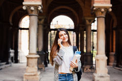 Gorgeous happy student holding notebooks speak phone on campus at college. Gorgeous happy student holding notebooks speak on phone on campus Royalty Free Stock Image