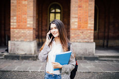 Gorgeous happy student holding notebooks speak phone on campus at college. Gorgeous student holding notebooks speak phone on campus at college Stock Photos