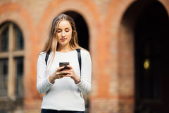 Gorgeous happy student holding notebooks texting on phone at campus at college. Gorgeous happy student holding notebooks texting on campus at college Stock Photography