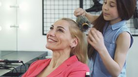 Gorgeous happy woman enjoying getting a new hairstyle by her cute daughter royalty free stock images