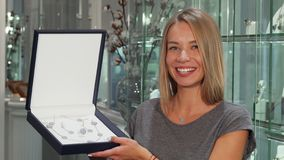Gorgeous happy woman smiling to the camera holding expensive jewelry set. Attractive female customer examining silver or platinum jewelry for sale. Shopping royalty free stock photo