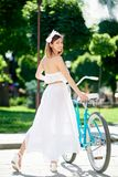 Beautiful happy woman riding bike in the city. Gorgeous happy young woman smiling to the camera over her shoulder walking with her bicycle in the park on a warm royalty free stock photography
