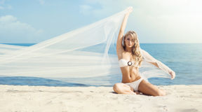 Gorgeous, hot girl in white bikini posing on the beach with blow Royalty Free Stock Photography