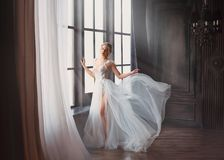 Gorgeous image of graduate in 2019, girl in long white light gentle flying dress with bare leg stands alone, swan. Princess before performing on ballet stage stock photo
