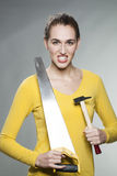 Gorgeous independent girl willing to DIY and fixing home herself. Female DIY concept - self-assured beautiful young woman holding saw and hammer to prove her Stock Images