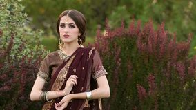 Gorgeous Indian girl in Sari costume in a park. Beautiful hindu girl in traditional costume sari of dark red color on the background of green grass and looking stock footage