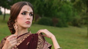 Gorgeous Indian girl in Sari costume in the park. stock video footage