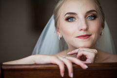 Gorgeous innocent blonde bride posing while sitting on chair, fa. Ce closeup Stock Image