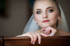 Gorgeous innocent blonde bride posing while sitting on chair, fa. Ce closeup Royalty Free Stock Photography