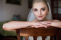 Gorgeous innocent blonde bride posing while sitting on chair, fa. Ce closeup Royalty Free Stock Images