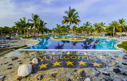 Gorgeous inviting view of luxury swimming pool and hotel grounds in tropical garden Royalty Free Stock Photo