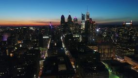 Gorgeous 4k drone aerial panorama flyover in orange sunset evening sky at night light big city Philadelphia cityscape stock video