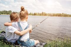 Gorgeous kids are sitting together near lake and hugging each other. Girl is fishing. She is holding fish-rod. They are. Alone there Stock Photography