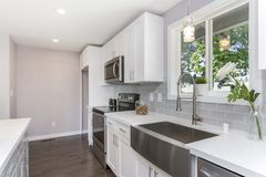 Gorgeous kitchen with a farm sink. Gorgeous kitchen with white cabinets and farm sink royalty free stock images