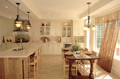 Gorgeous kitchen with large window's. A nice bright kitchen in a new house with a big table and chairs an one wall only a large window and light fixture royalty free stock photography