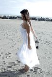 Gorgeous lady on the beach dancing with white dress Royalty Free Stock Photography