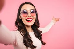 Gorgeous lady in casual shirt with red lips posing in trendy sun. Glasses on camera with smile while taking selfie isolated over pink background Stock Image